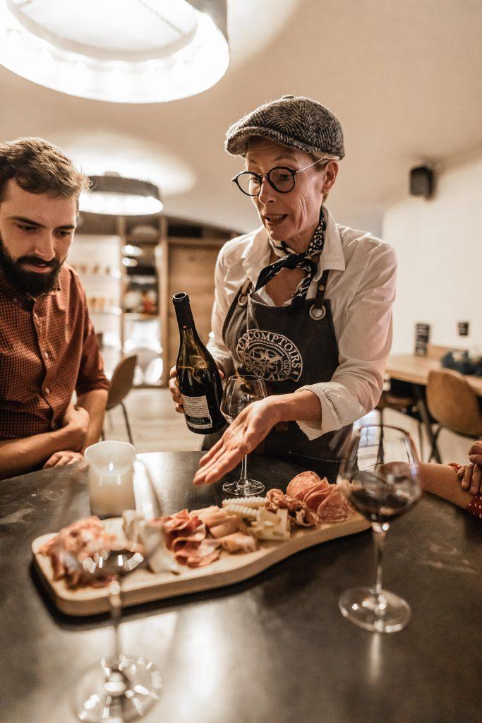 Ftamboise gérante du bar à vins conseillant les clients sur les produits